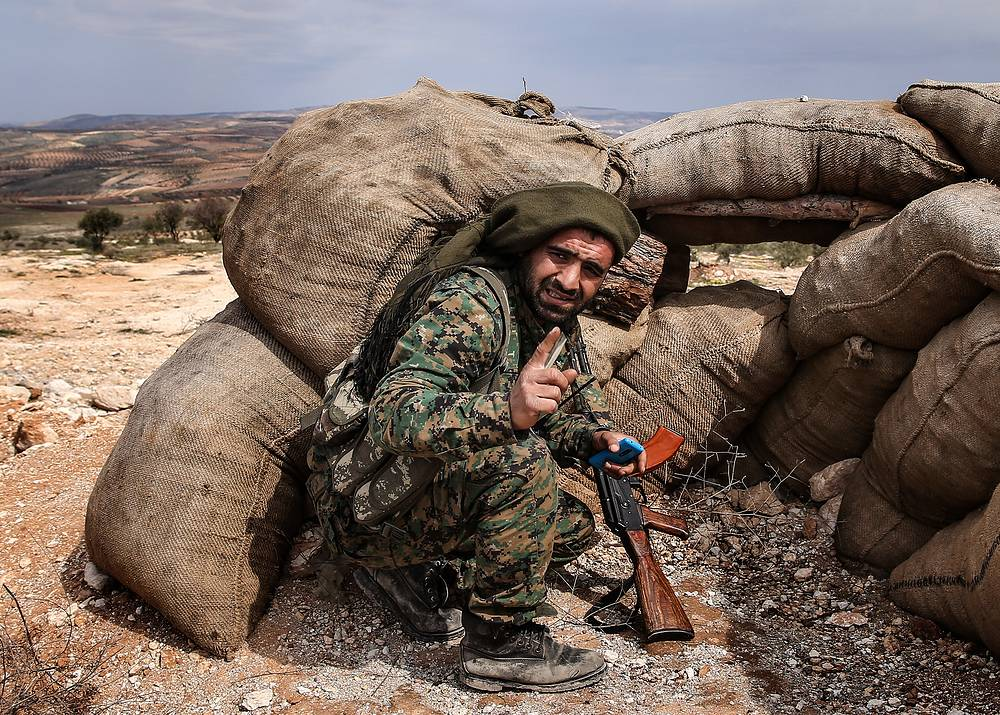 A Kurdish fighter surveying the area from an elevation near the town of Azaz on the Syrian-Turkish border