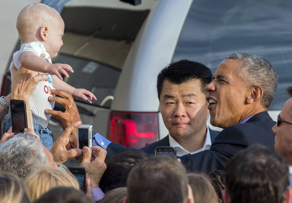 US President Barack Obama reaches out to a baby at John F. Kennedy International Airport in New York, September 18