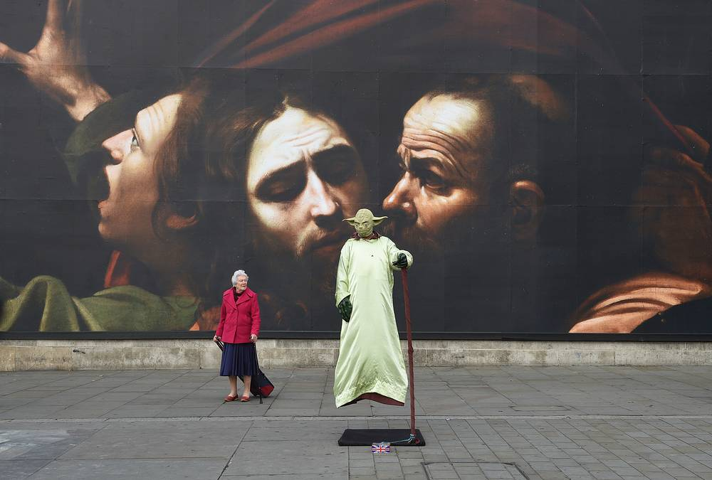 A street performer in 'Yoda' costume stands in front of a giant poster, a detail of a painting by Caravaggio: 'The Taking of Christ' in London, Britain, October 12