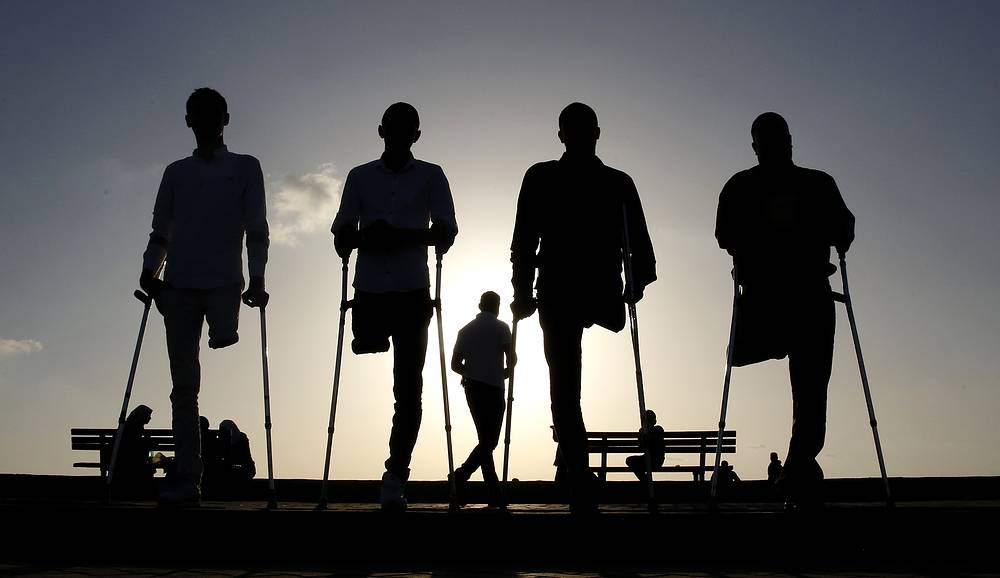 Four Palestinians who were injured during conflicts walk by the sea at Gaza's small fishing harbor, October 24