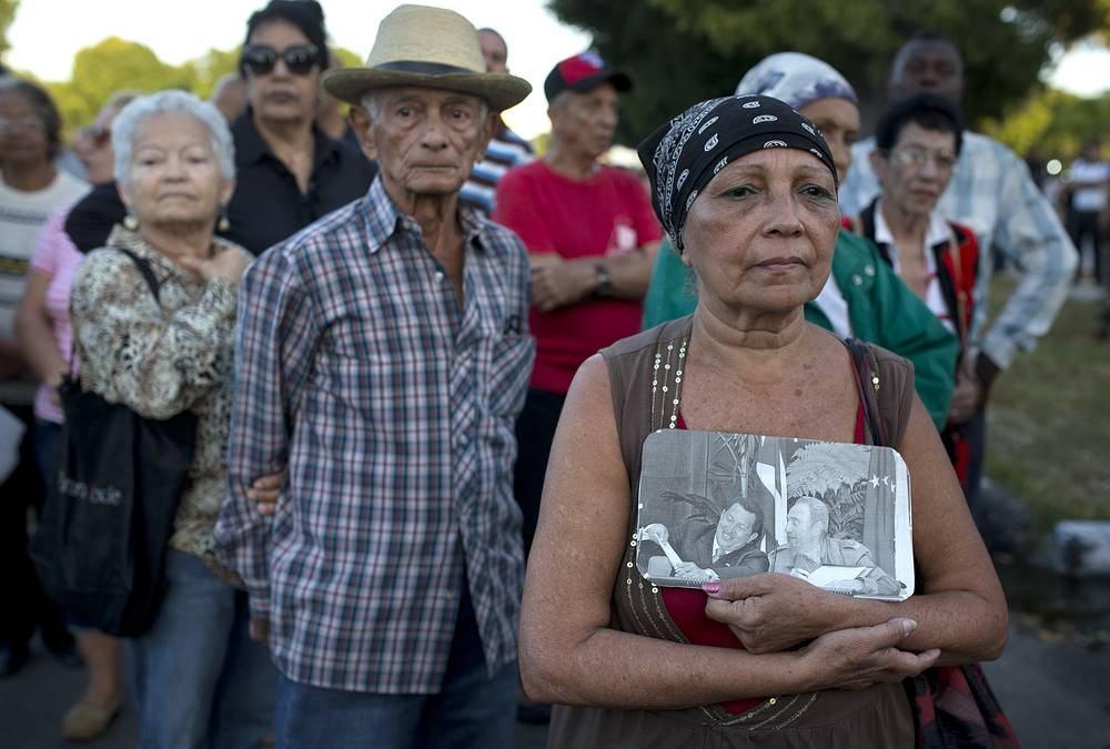Woman with a picture of Fidel Castro and Hugo Chavez  waiting in line to enter Revolution Square to render homage to Fidel Castro, in Havana