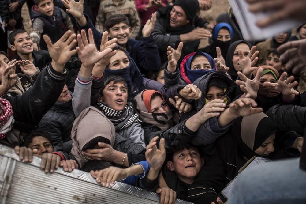 Iraqi displaced people plead for food during an aid distribution in Khazer camp in Iraqi Kurdistan, December 17