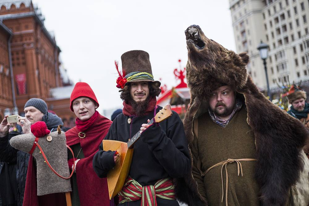 Performers entertain people while they celebrate Maslenitsa, or Pancake week at Manezhnaya Square, near Red Square in Moscow