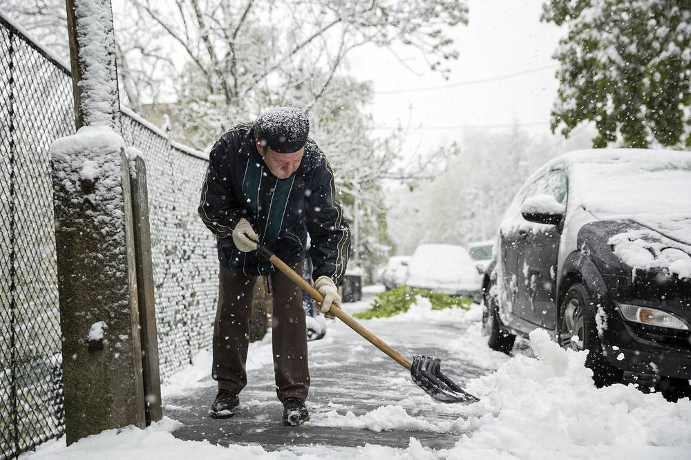 A man shovels snow from the sidewalk in Budapest, Hungary, April 19