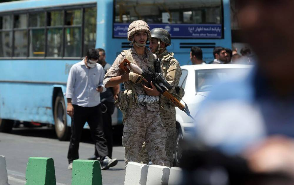 Iranian army soldiers stand near parliament building during an attack in Tehran