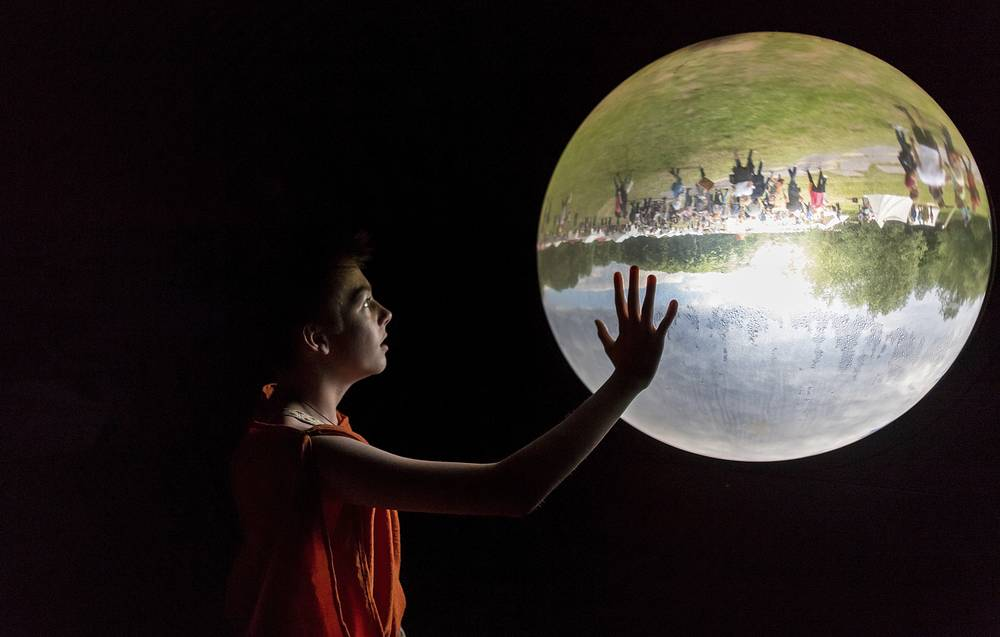 A boy looks at a glass bowl showing the outside upside down in a museum in Bramsche-Kalkriese, Germany, June 4