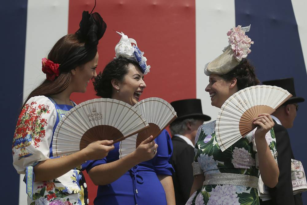Racegoers use fans to cool off in the heat at the Royal Ascot horse race