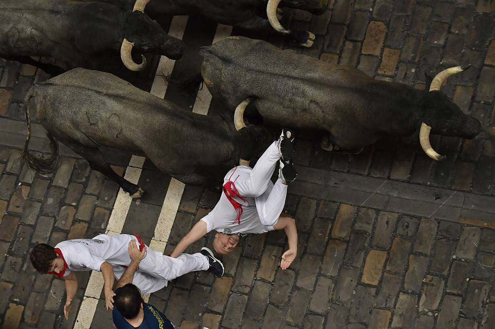 A revellers falls in front of Jose Escolar fighting bulls