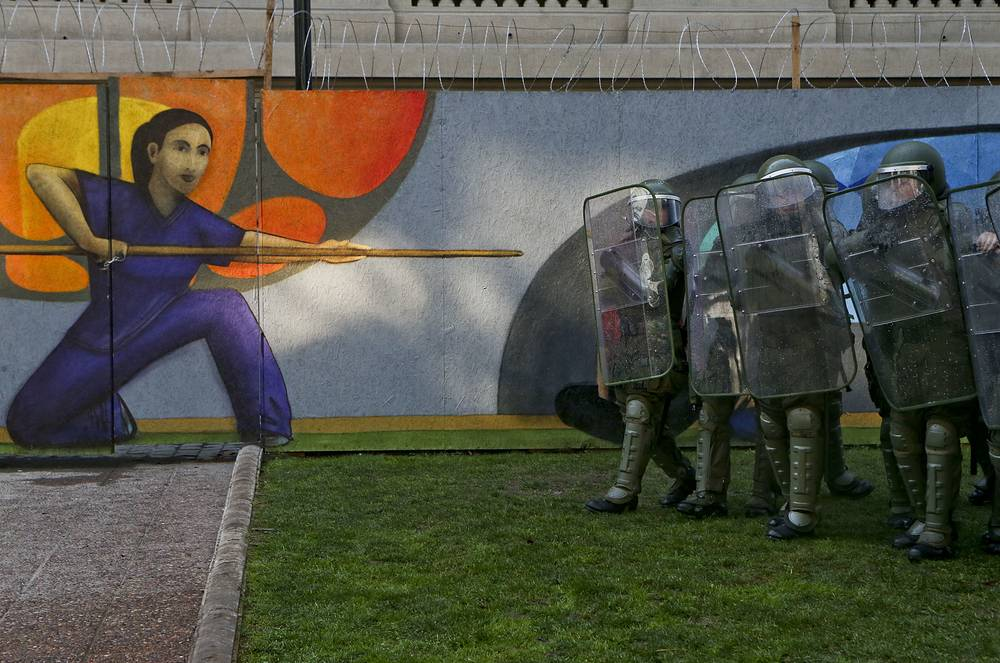 """Police confront people protesting the self-proclaimed """"Bus of freedom"""" which rejects transgender children in schools, next to an art museum in Santiago, Chile, July 10"""