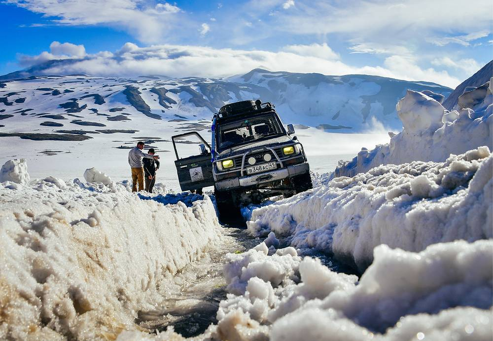 Participants in a jeep tour stop at the Vilyuchinsky pass as they ascend the active Mutnovsky volcano in the southern part of the Kamchatka Peninsula, Russia, July 18
