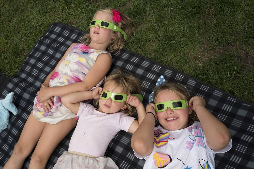 Children watch the solar eclipse from a New York City park
