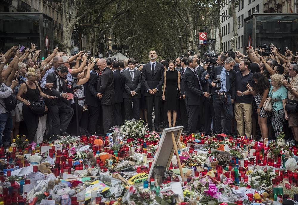 People take photos as Spain's King Felipe and Queen Letizia pay their respects at a memorial tribute adorned with flowers, messages and candles honoring the terror attack victims at the Las Ramblas promenade, Barcelona, Spain, August 19