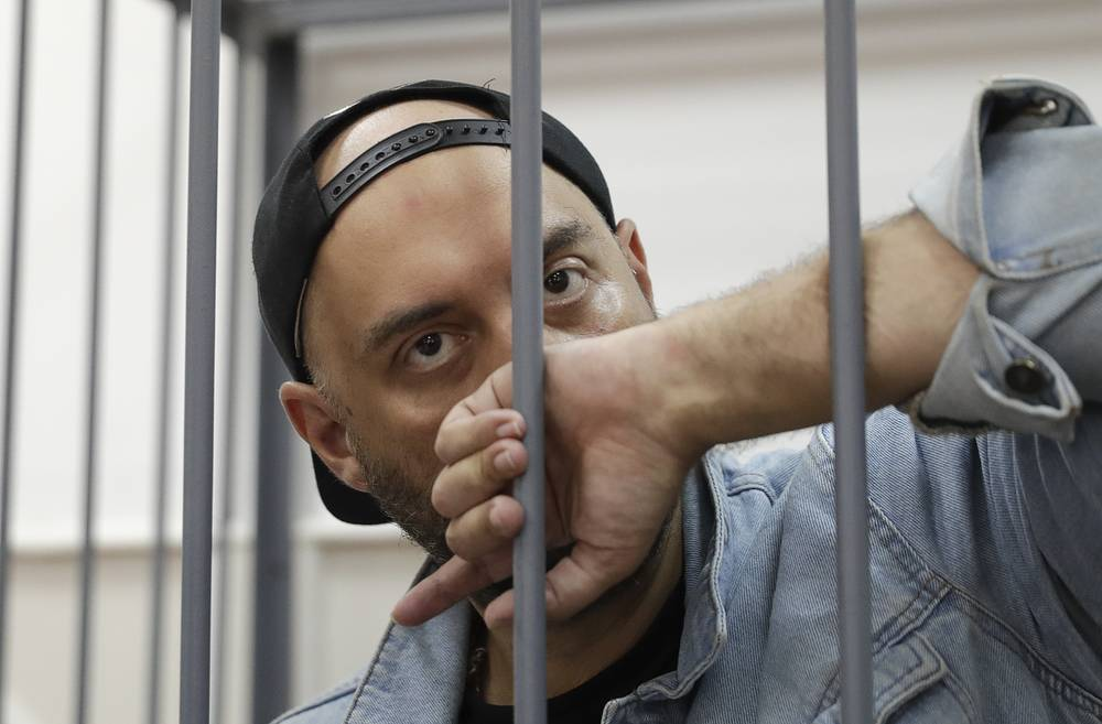 Russian theater director Kirill Serebrennikov, who was detained and accused of embezzling state funds, looks on inside the defendants' cage as he attends a hearing on his detention at a court in Moscow, Russia, August 23