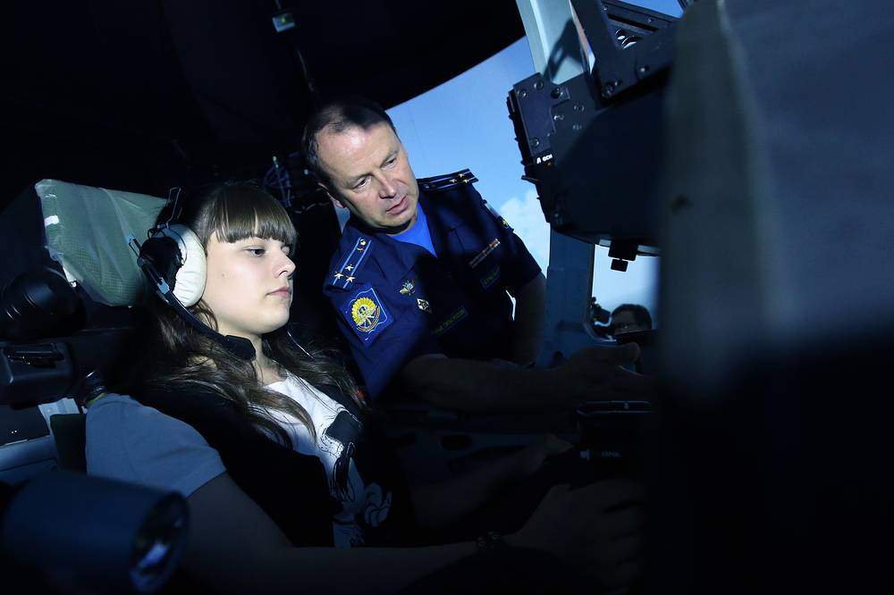 A female applicant and a military officer in a flight simulator