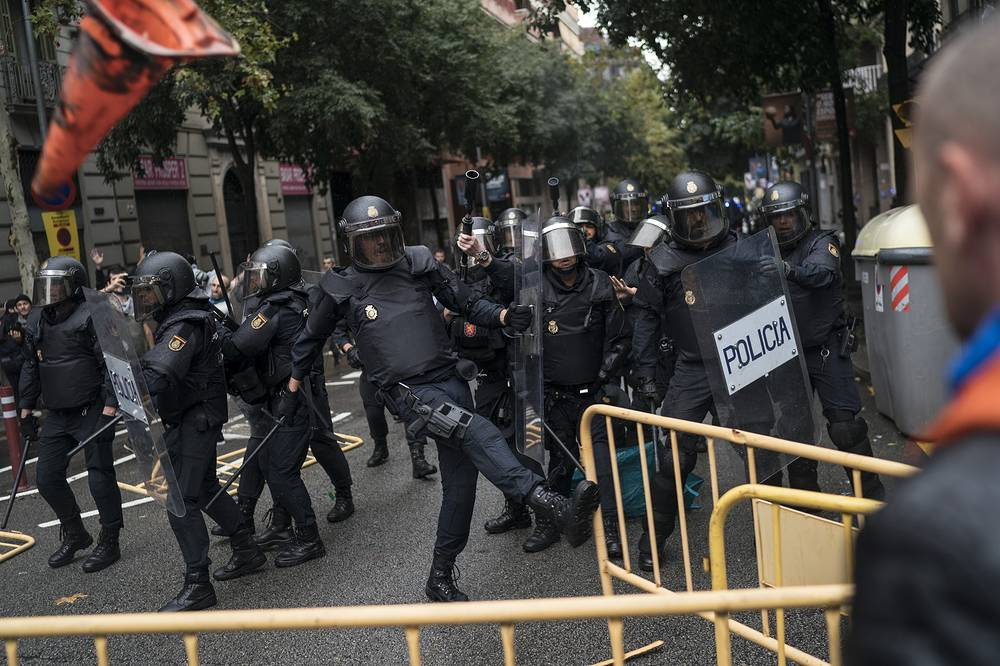 Spanish riot police removes fences thrown by people to them as they try to prevent people from reaching a voting site at a school assigned to be a polling station by the Catalan government in Barcelona