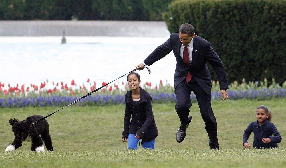 US President Barack Obama, his daughters Malia and Sasha play with their dog Bo on the South Lawn of the White House in Washington, 2009