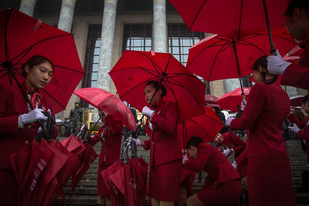 Chinese stewardesses carry umbrellas during rain before the opening ceremony of the 19th National Congress of the Communist Party of China at the Great Hall of the People in Beijing, China, October 18