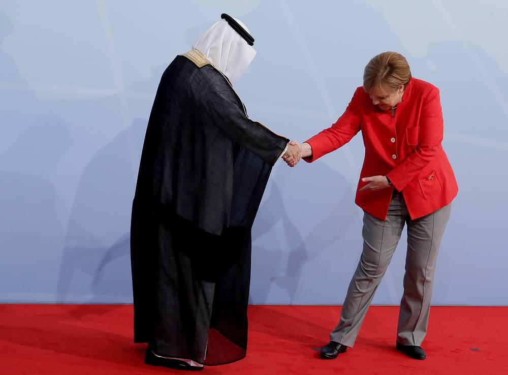 German Chancellor Angela Merkel shakes hands with Saudi Arabia's former finance minister, Ibrahim al-Assaf, at the G20 summit in Hamburg, Germany, 2017