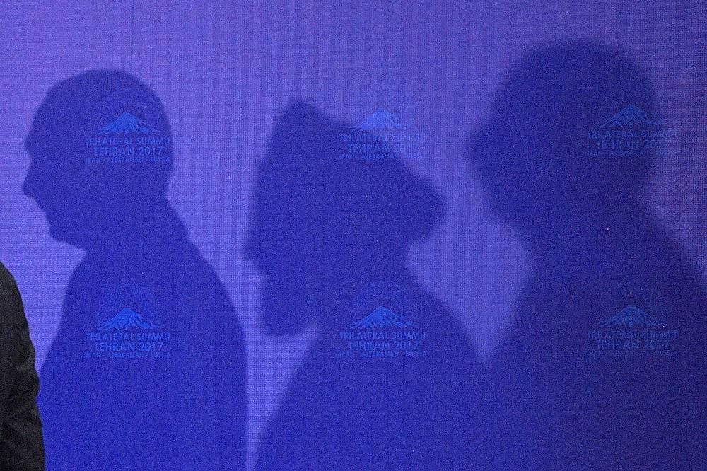 Shadows cast by Russia's President Vladimir Putin, Iran's President Hassan Rouhani, and Azerbaijan's President Ilham Aliyev during a trilateral meeting in Tehran, Iran, November 1