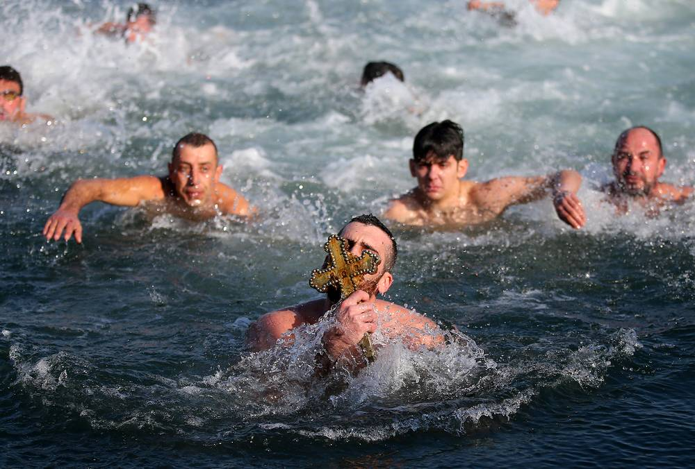 Greek Orthodox swimmers take part in an annual race to retrieve a wooden crucifix thrown into the Bosphorus waters at the Golden Horn in Istanbul, Turkey, January 6