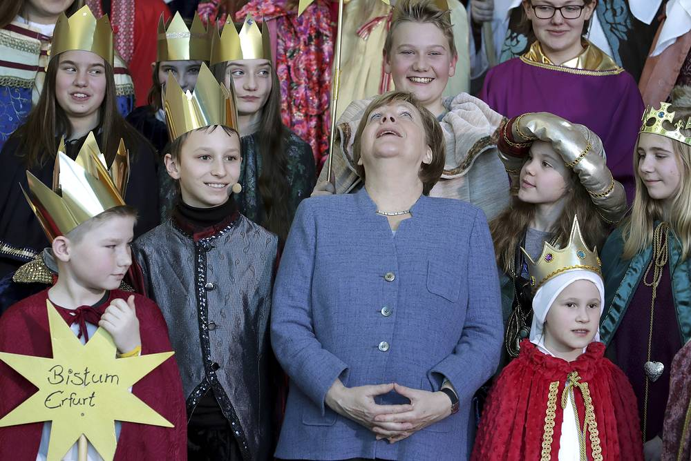 German chancellor Angela Merkel looks up as she sings with carolers during a reception for carol singers from all over Germany at the chancellery in Berlin, Germany January 8