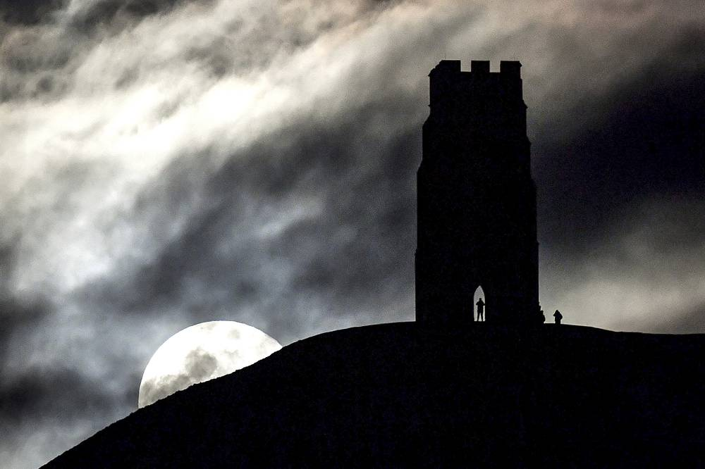 The moon rises behind Glastonbury Tor, southwestern England
