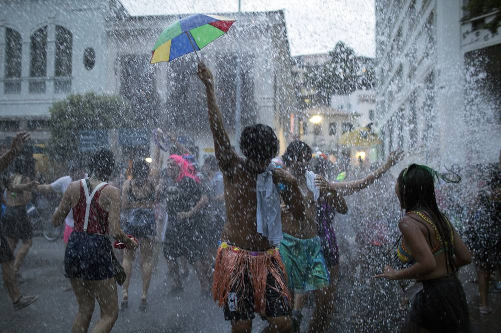"People cool off in water during the ""Escravos da Maua"" block party, as part of pre-Carnival celebrations in Rio de Janeiro"