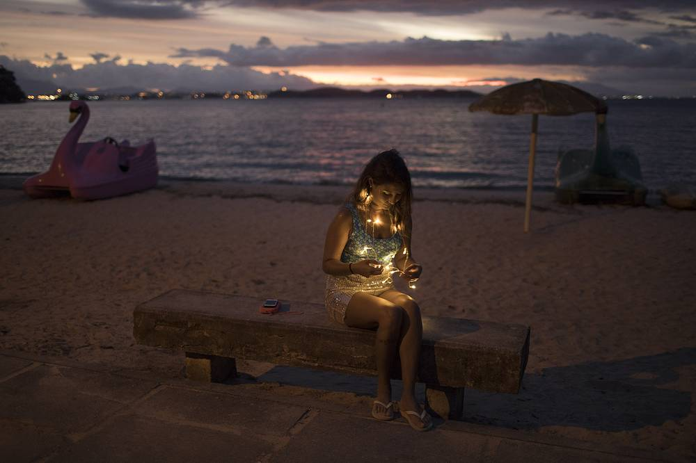 A woman wearing lights sits on a bench as she takes part in the Perola da Guanabara street party at Paqueta island in Guanabara Bay in Rio de Janeiro