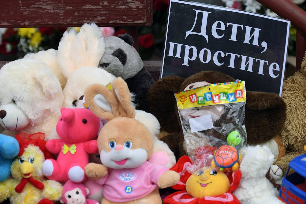 "Toys and a note reading ""Children, Forgive [Us]"" outside the Zimnyaya Vishnya shopping centre in Kemerovo"