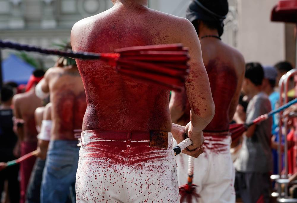 Filipino flagellants whip their backs in front of a church on Maundy Thursday in San Fernando, Philippines. Many Filipino Catholic penitents mark the Holy Week by submitting to different forms of physical penance in the hopes of being forgiven for their sins