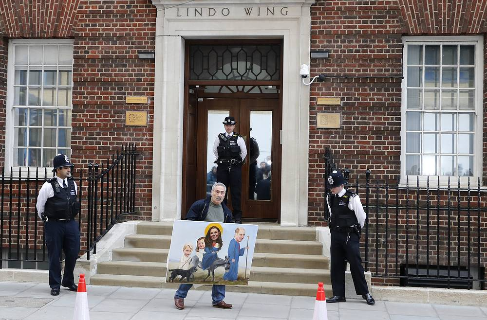 An artist with a painting walks past the Lindo wing at St Mary's Hospital in London