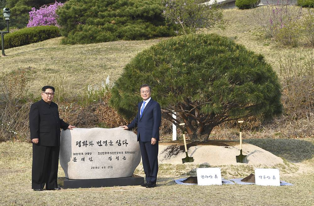 North Korean leader Kim Jong Un and South Korean President Moon Jae-in pose for photo after they planted a pine tree near the military demarcation line at the border village of Panmunjom