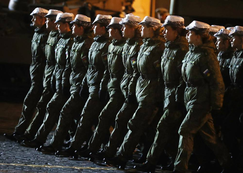 Female soldiers march in formation during a night rehearsal of a Victory Day military parade