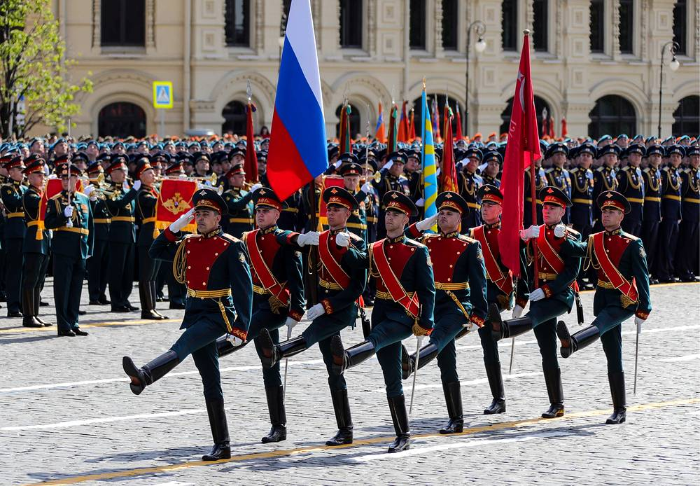 Servicemen carry a Russian national flag and Victory Banner during a Victory Day military parade in Moscow