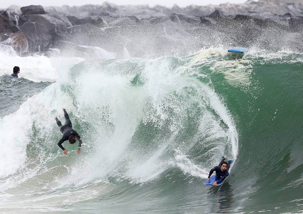 Bodyboarders are swallowed by a huge wave at 'The Wedge' surf spot as a Pacific Ocean storm swell hits Southern California in Newport Beach, California, May 23