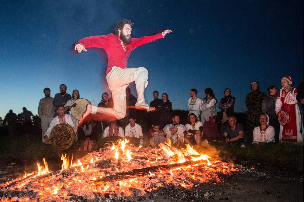 A man jumps over a bonfire