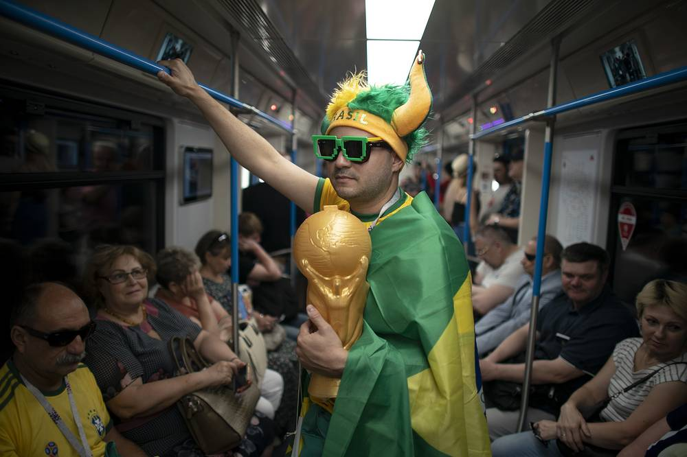 A fan wrapped in a Brazilian flag travels on the subway to Spartak Stadium in Moscow
