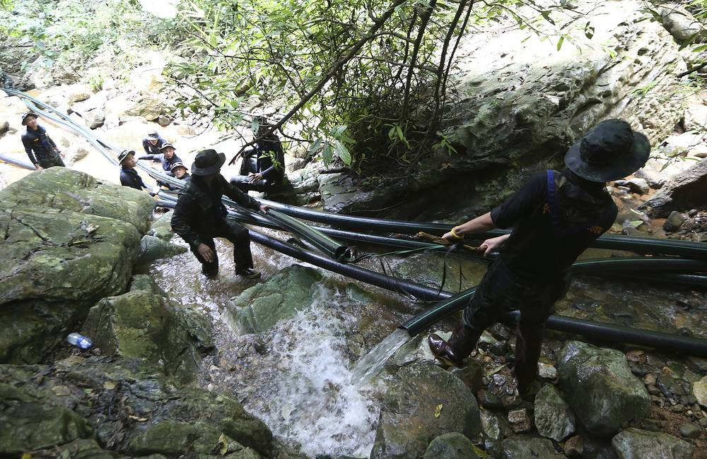 Thai soldiers drag water pipes that will help bypass water from entering the cave