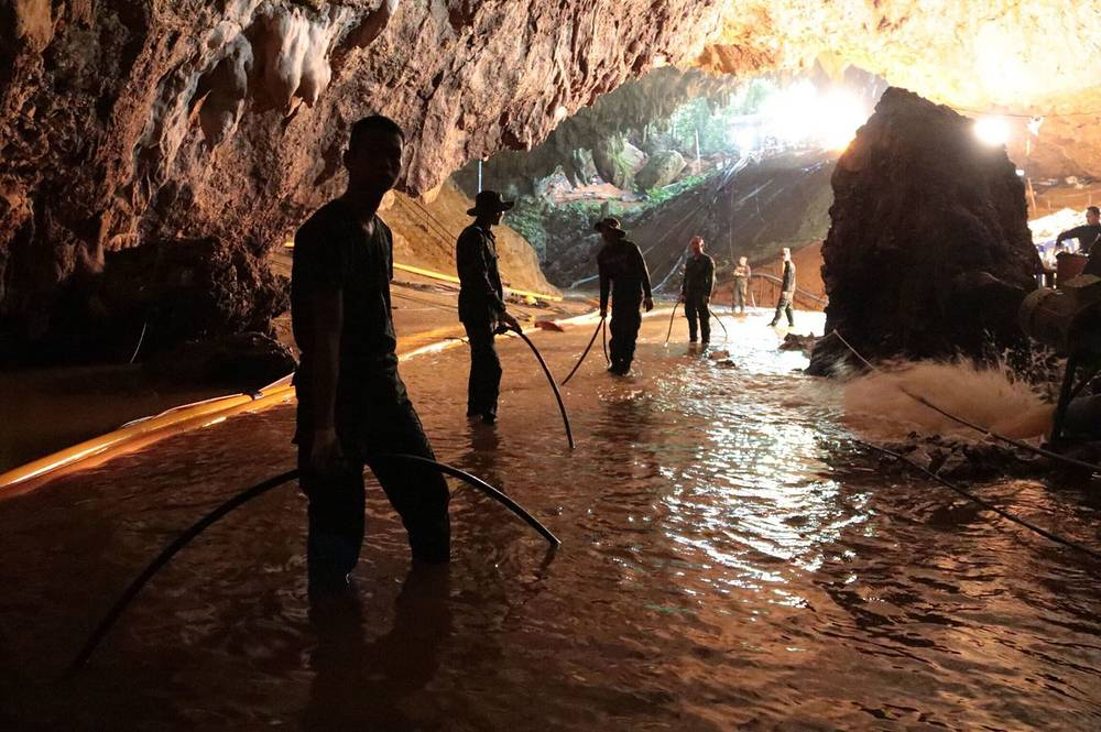 Thai rescue teams arrange water pumping system at the entrance to the cave