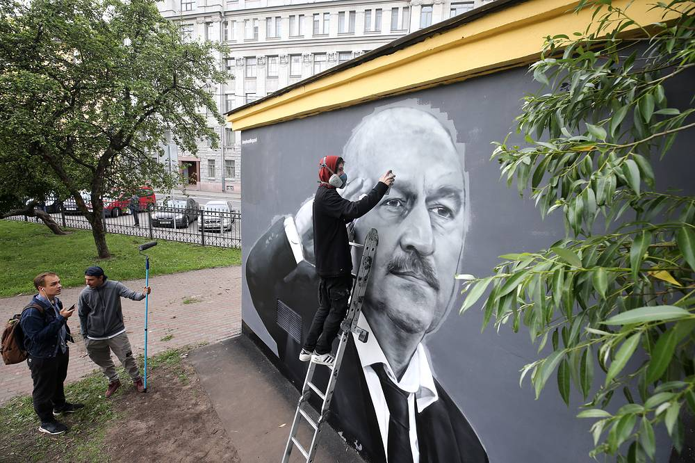 Street artists retouch mural depicting Russian men's national football team head coach Stanislav Cherchesov as it was damaged following the 2018 FIFA World Cup quarterfinal between Russia and Croatia