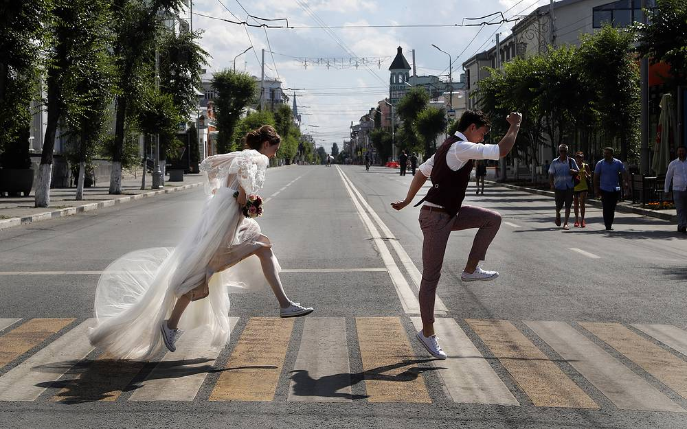 Newlyweds pose on a zebra crossing for wedding photographers during the 2018 soccer World Cup in Samara, July 8