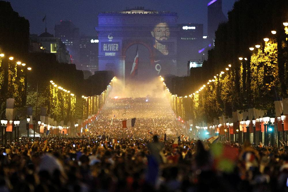 The name of French striker Olivier Giroud is projected onto the Arc de Triomphe as football fans invade the Champs Elysees avenue after France won the World Cup final match between France and Croatia, Paris, July 15