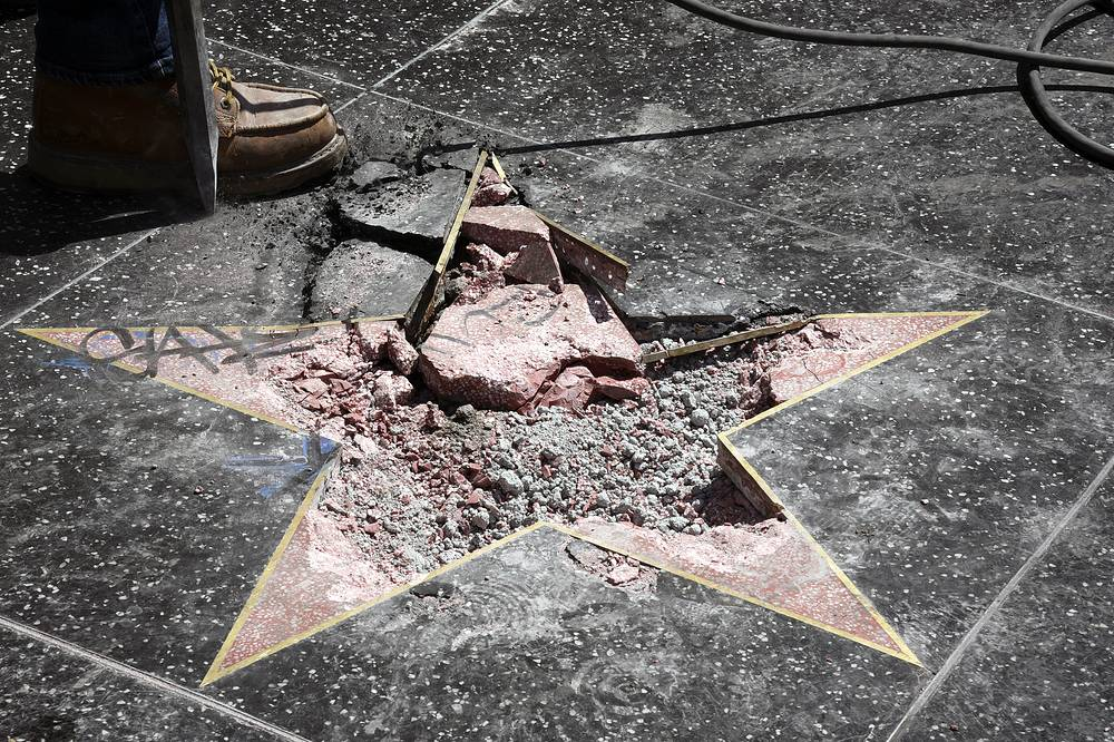 Workers remove shattered concrete debris from President Donald J. Trump's star on the Hollywood Walk of Fame after it was destroyed overnight in the Hollywood section of Los Angeles, July 25
