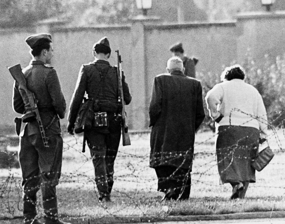 An East German couple is turned away from the border, blocked by East German soldiers and barbed wire, after trying to cross into West Berlin, 1961