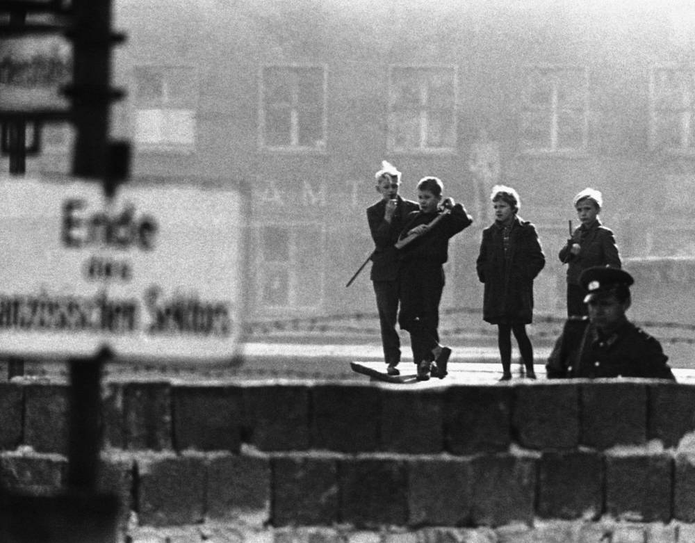 "East Berlin youngsters with toy guns play at being ""people's police"" as they look over the concrete wall in the Bernauer Strasse, 1961"
