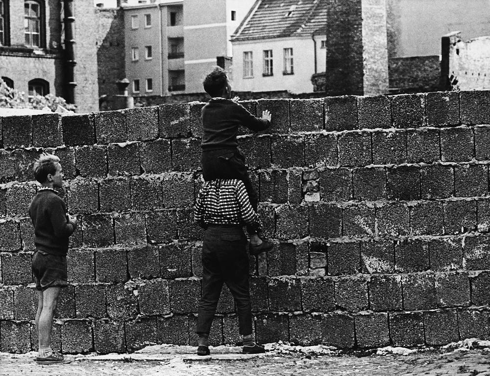 A boy sitting on the shoulders of another child peers at the Liesen Street in Wedding, West Berlin, over the wall towards the eastern part of the city, 1961