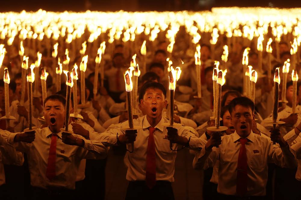 North Korean youths march during the torch parade at the Kim Il Sung Square in conjunction with the 70th anniversary of North Korea's founding day in Pyongyang