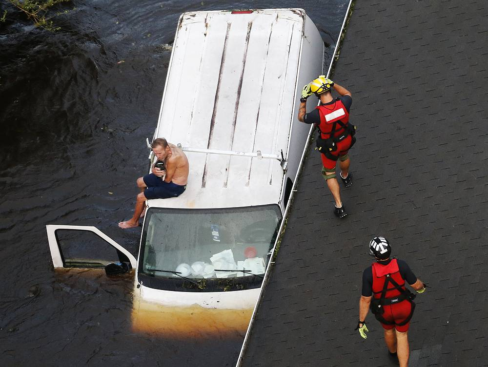 US Coast Guard rescue swimmer approach to a man on a stranded van in Pollocksville