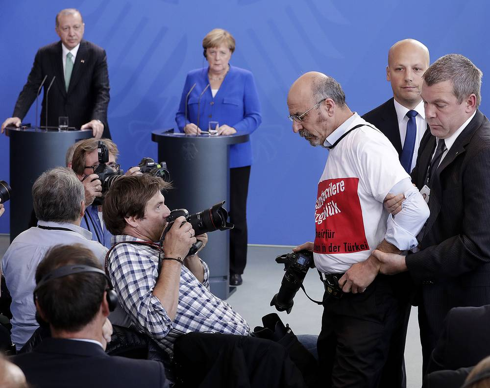 A protester is taken away as Turkish President Recep Tayyip Erdogan and German Chancellor Angela Merkel give a joint press conference in Berlin, September 28