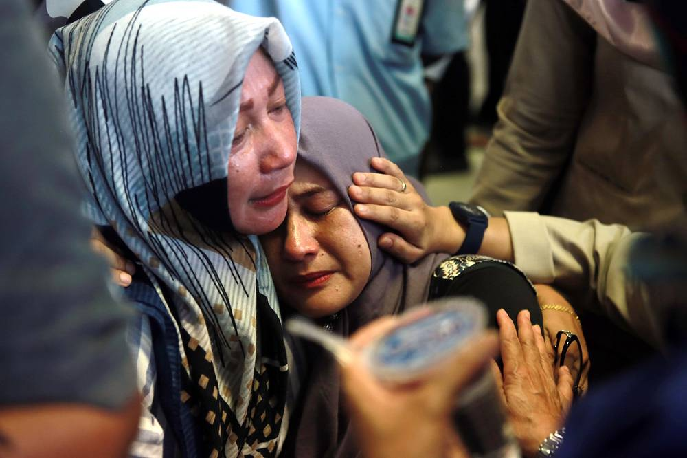 Relatives of the plane crash victims cry as they wait for the news at the airport in Pangkalpinang, Indonesia